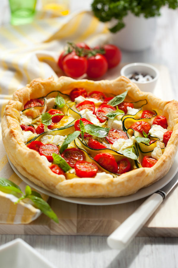 Quiche with tomato and zucchini stock images