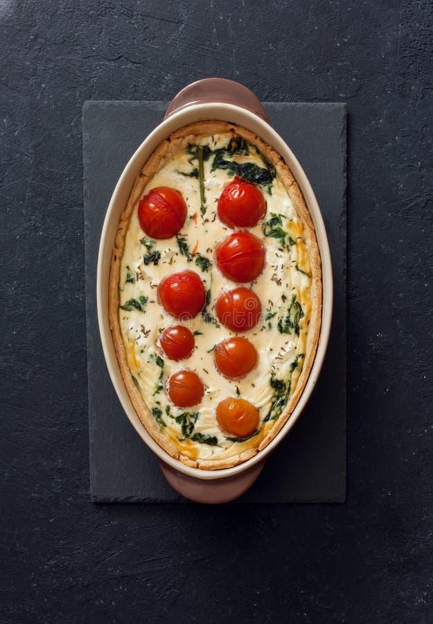 Quiche végétale de tarte avec des tomates et des épinards au-dessus de Ba noir photos libres de droits