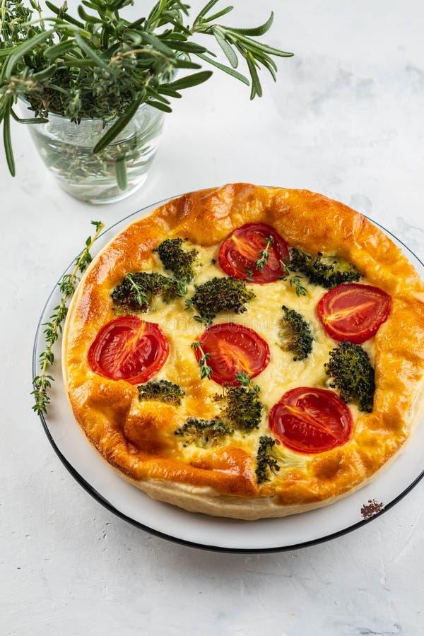 Quiche végétale de tarte avec le brocoli, les tomates et le fromage à pâte molle sur le fond blanc photo libre de droits
