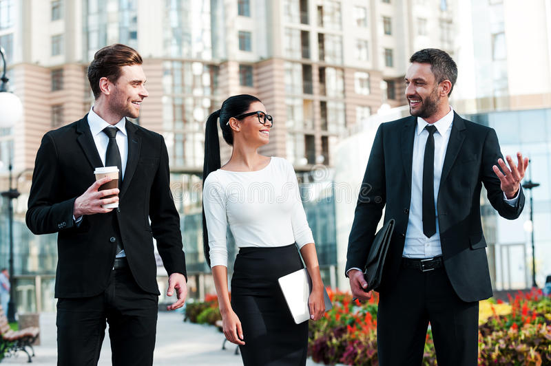 Quick briefing before meeting. Three cheerful young business people talking to each other while walking outdoors royalty free stock image