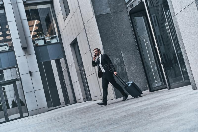 Quick business talk. Full length of young man in full suit talking on the phone and smiling while walking outdoors royalty free stock image