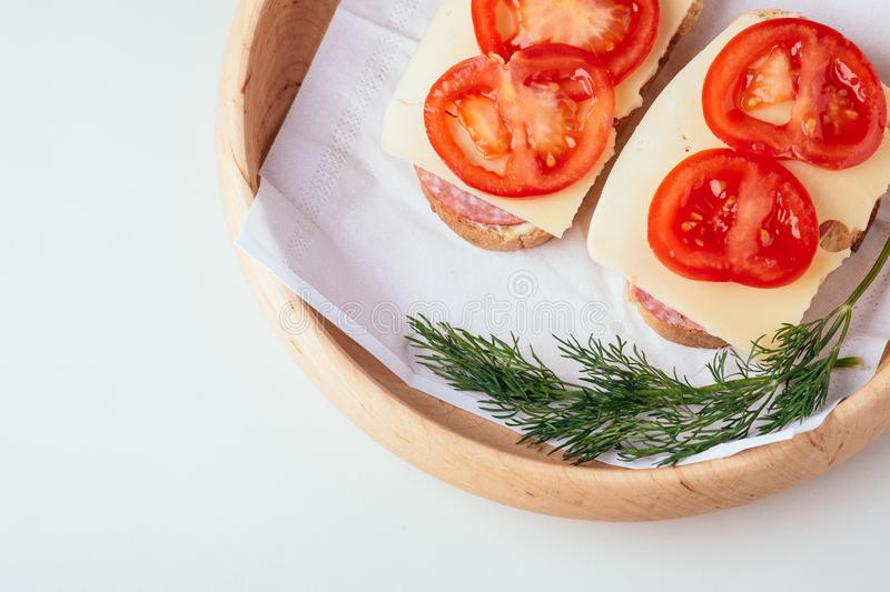 Quick cooking sandwiches with ham meat cheese tomato dill on wooden plate stock photography