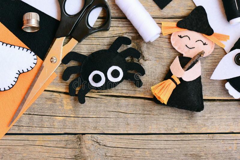 Quick Halloween crafts. Felt witch doll, spider decorations on a vintage wooden background. Needlework tools and materials stock photography
