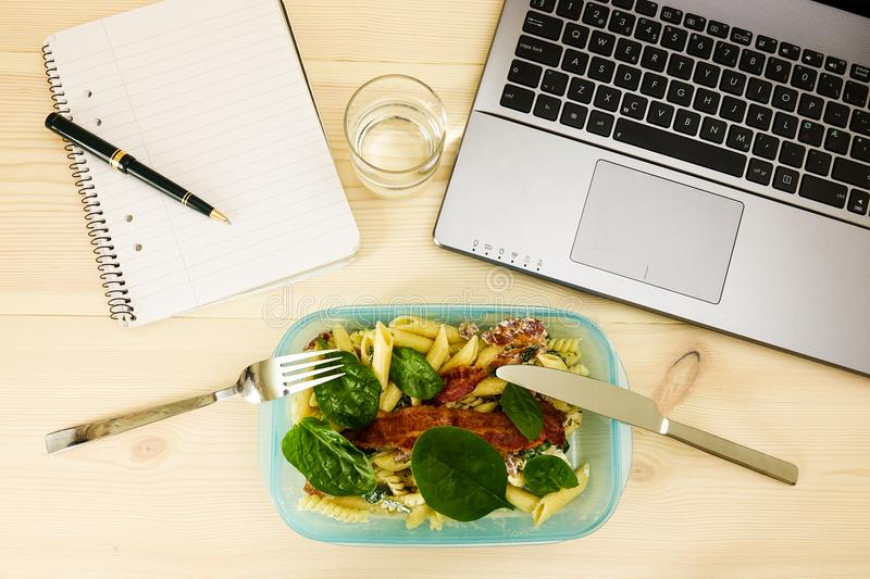 Quick Lunch, lunch box in front of laptop stock image