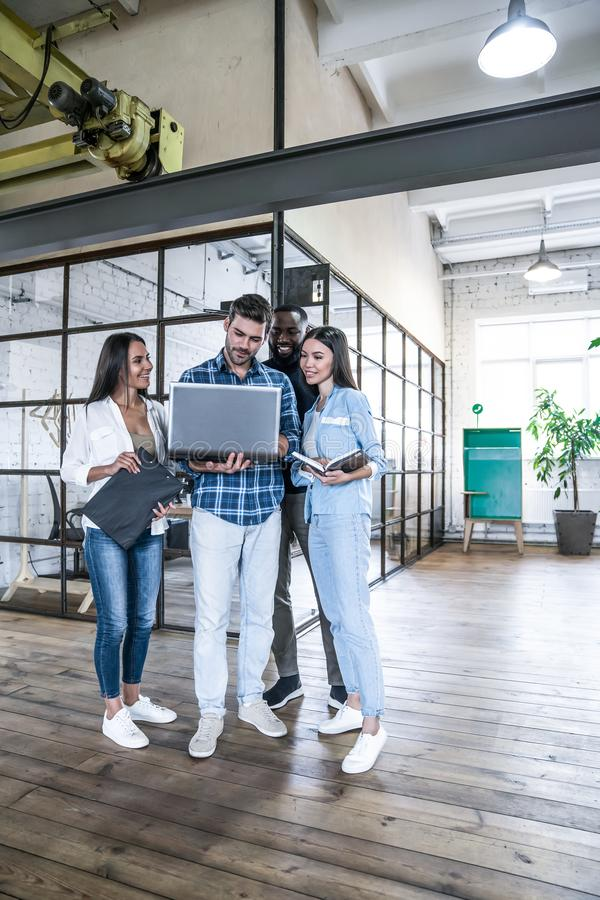 Quick meeting. Full length of young business people in smart casual wear working together and smiling while standing in the office royalty free stock photography
