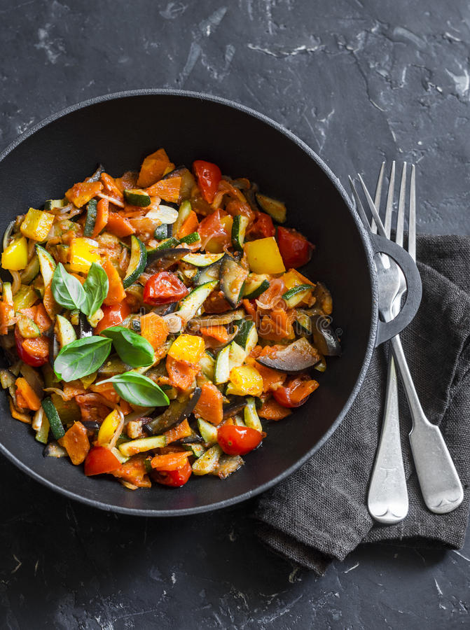 Quick ratatouille in a cast iron skillet on a dark background, top view. Steamed vegetables - vegetarian food stock photo