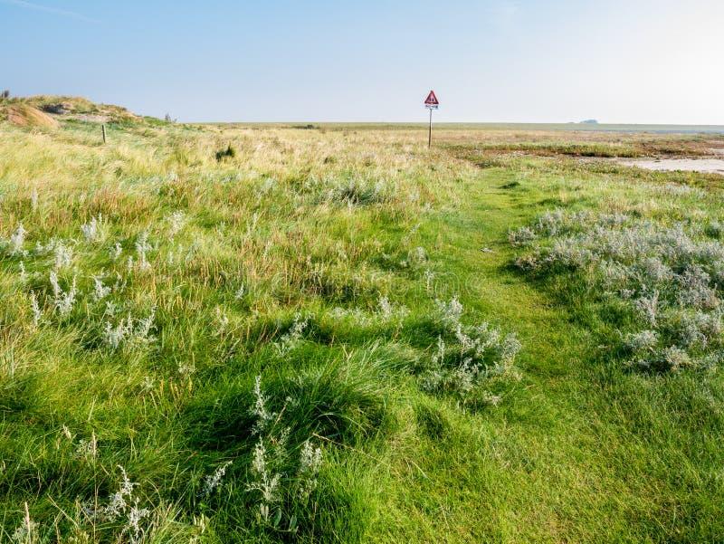 Quicksand niebezpieczeństwa znak ostrzegawczy w nabrzeżnym saltmarsh Zachodnia Fryzyjska wyspa Schiermonnikoog Waddensea w czasie fotografia stock