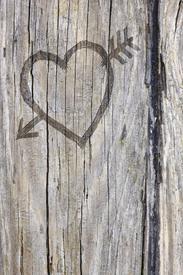 Quiera la pintada del corazón y de la flecha tallada en la madera imágenes de archivo libres de regalías