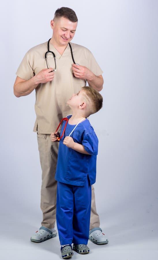 Quiera ser doctor como papá Juego lindo del doctor del juego del niño M?dico de cabecera : Doctor del padre con el estetoscopio fotos de archivo