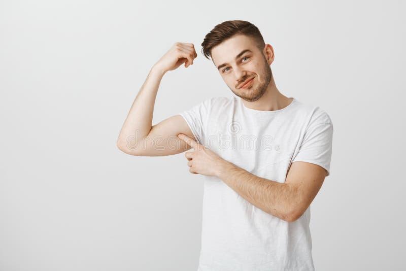 Quiera tocar mi bíceps fuerte Varón hermoso lindo y coqueto con la barba en cabeza inclinable y la sonrisa de la camiseta casual  fotos de archivo libres de regalías