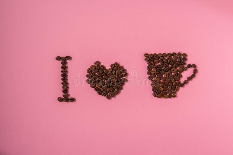 Quiero el café Texto de los granos de café en un fondo rosado fotografía de archivo