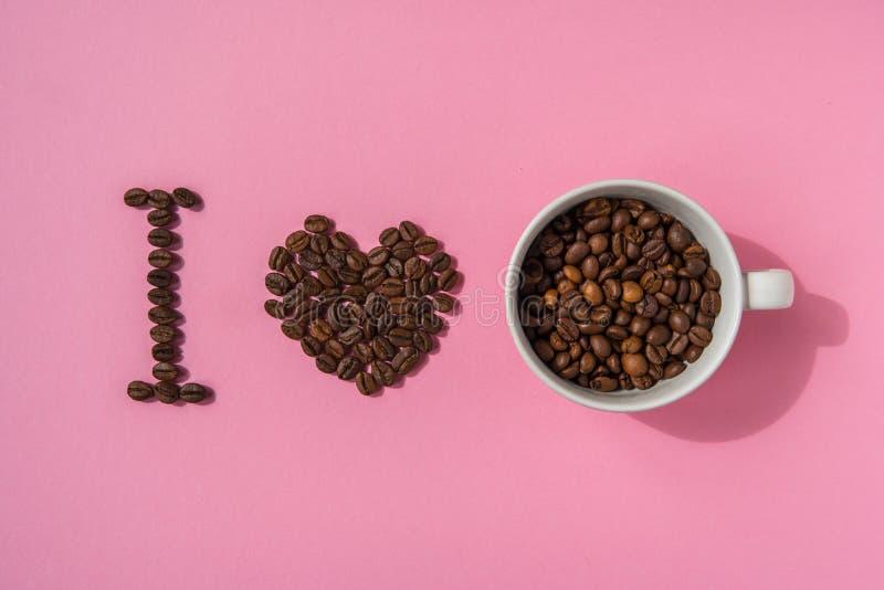Quiero el café Texto de los granos de café en un fondo rosado foto de archivo