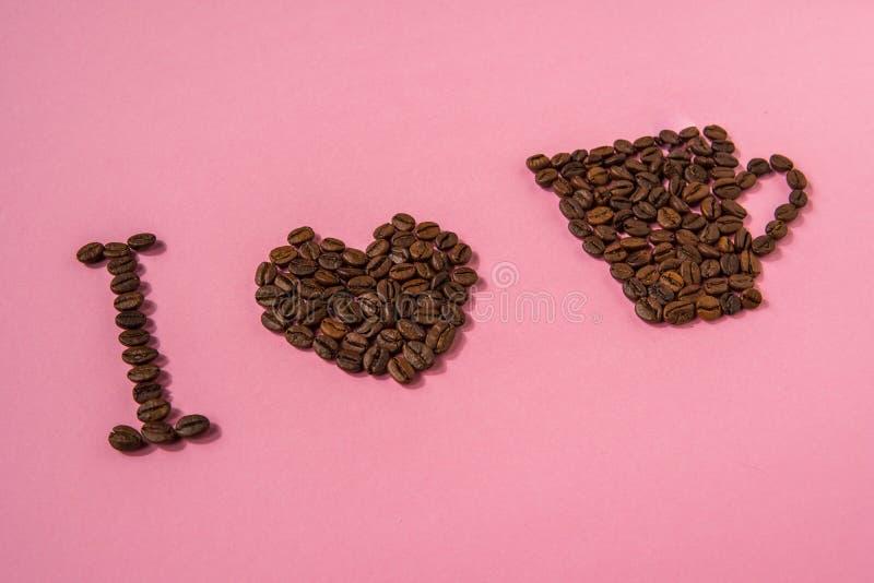 Quiero el café Texto de los granos de café en un fondo rosado fotos de archivo libres de regalías