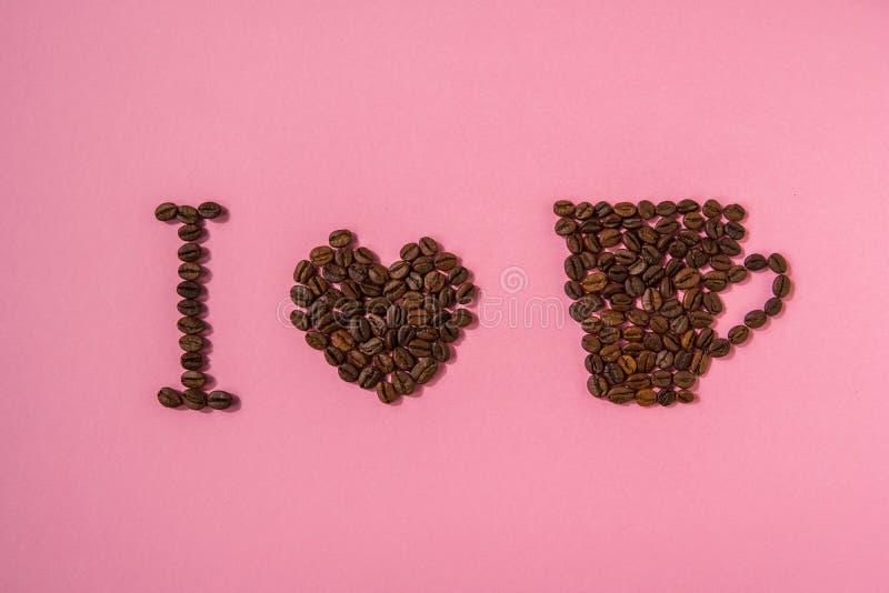 Quiero el café Texto de los granos de café en un fondo rosado imagen de archivo libre de regalías