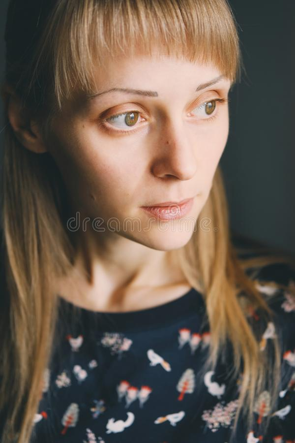 A quiet and beautiful girl with long blonde hair looking to the side. Portrait of a young woman with moles on her face close-up stock photography