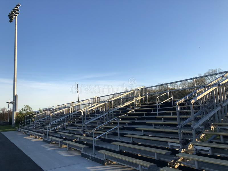 Quiet bleachers after the game is over. Empty game field. Football game is over. Bleachers are quiet. Empty bleachers. each. People have gone home. Sun is stock photography