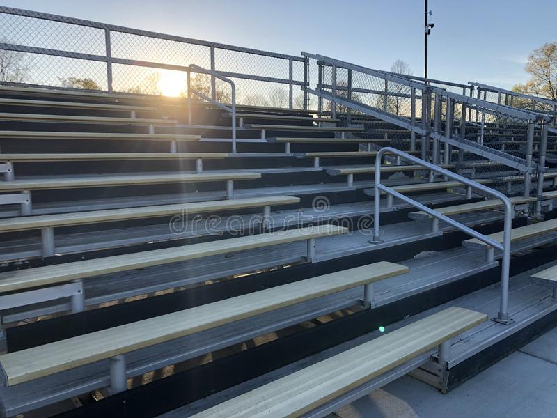Quiet bleachers after the game is over. Empty game field. Football game is over. Bleachers are quiet. Empty bleachers. each. People have gone home. Sun is royalty free stock photos