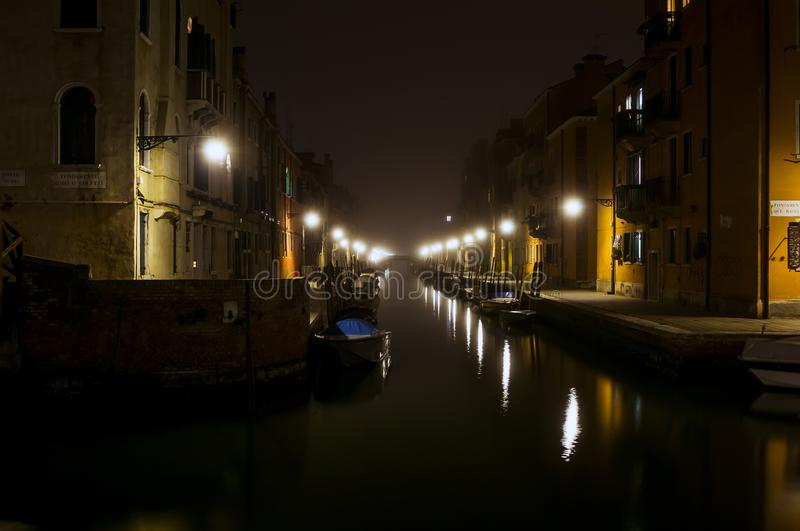 Quiet canal at night in Venice. Warm light of the street lights illuminates the street and reflected in waterways. Private boats are parked along the canal stock photo