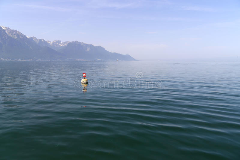 Quiet Lac Leman and Swiss Alps with snow caps near Montreux in Switzerland in summer.  royalty free stock photos