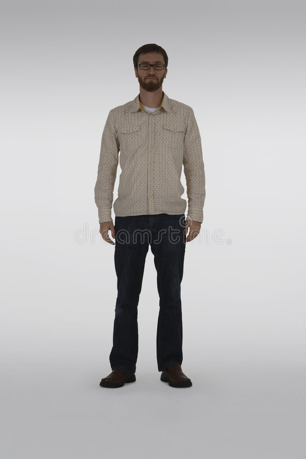 Quiet meditation. Full length photo of man a with beard standing inside a photo studio. He is wearing a cream Oxford shirt and denim jeans. The studio is dimly royalty free stock image