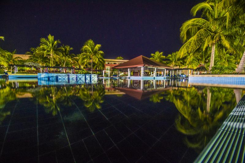 Quiet night at the pool in a tropical resort hotel. royalty free stock photography