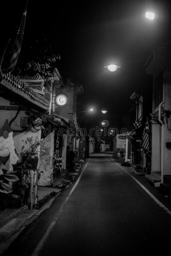 Quiet black and white street in the middle of night. Quiet night street with lights on the long street. there is no one royalty free stock photo
