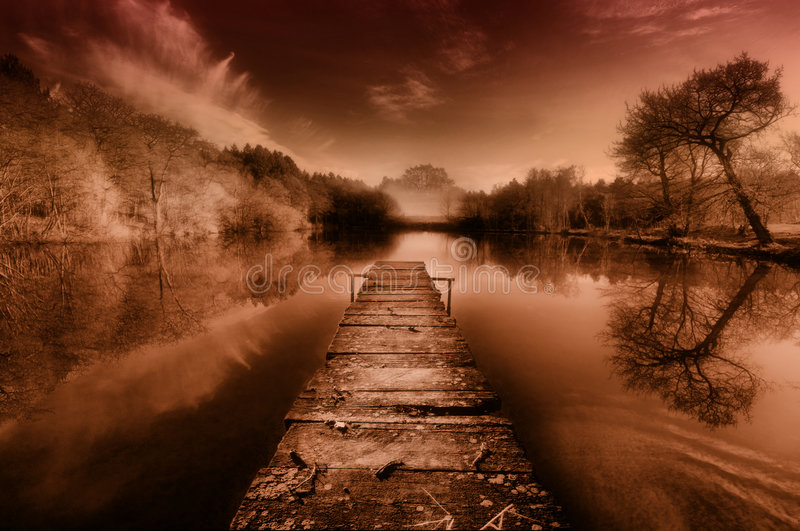 Quiet Pond at Dusk. A boardwalk extends over a tranquil pond at dusk royalty free stock image