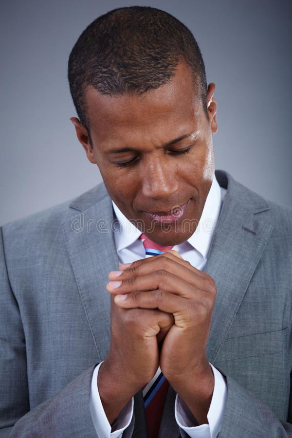 Quiet prayer. Smart businessman praying with his eyes closed stock photo