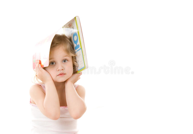 Quiet pretty little girl with book sitting on whit stock photo