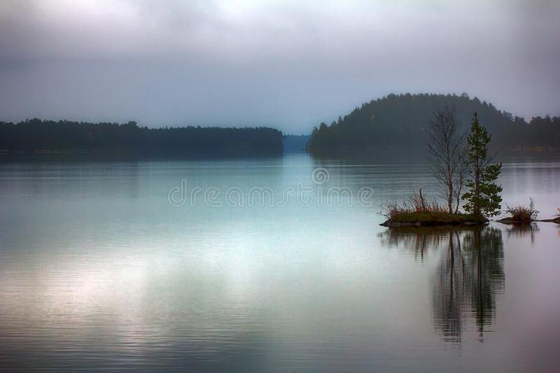 Quiet sad fall day on quiet lake. Brooding landscape with islets. Quiet sad fall day on serene lake, fog light stock image