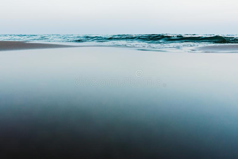 Quiet scene of a serene sea, with the background of the sand reflecting in the water the sky stock photos