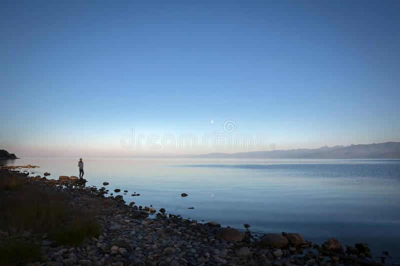 Quiet sunset over the river. The girl stands on the rocky shore. Summer calm evening, full moon royalty free stock photo