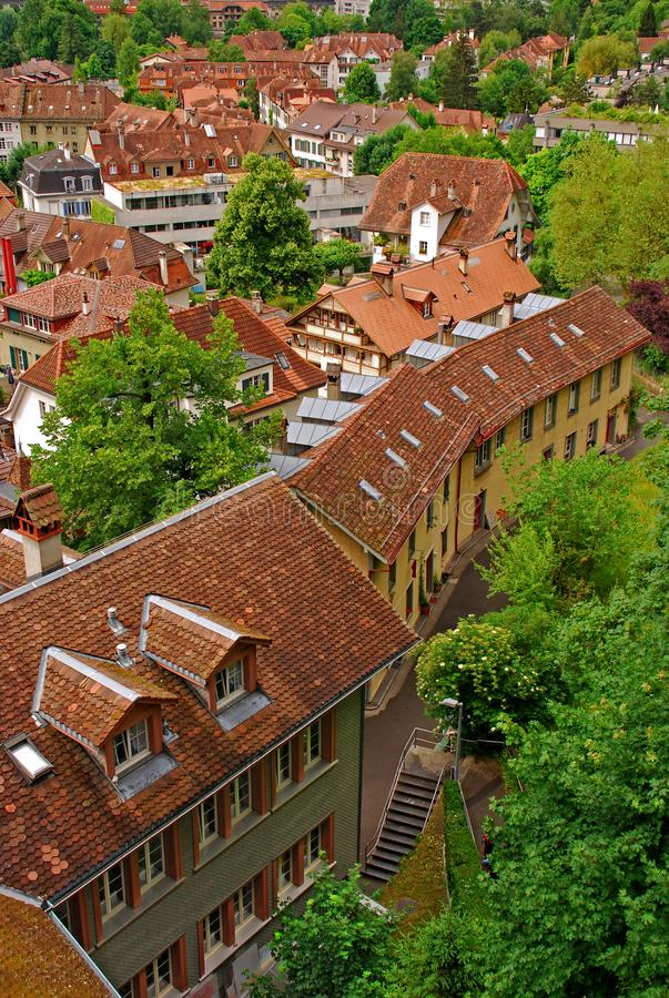 View of typical building architecture layered between many green trees behind Bern Parliament. A quiet and tranquil capital city of Switzerland around the Berne