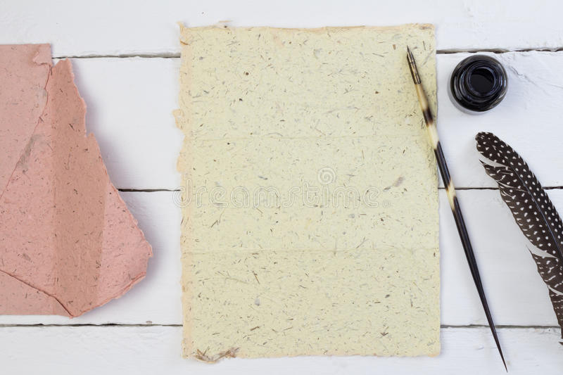 Quill pen, hand made paper and envelope on white royalty free stock photography
