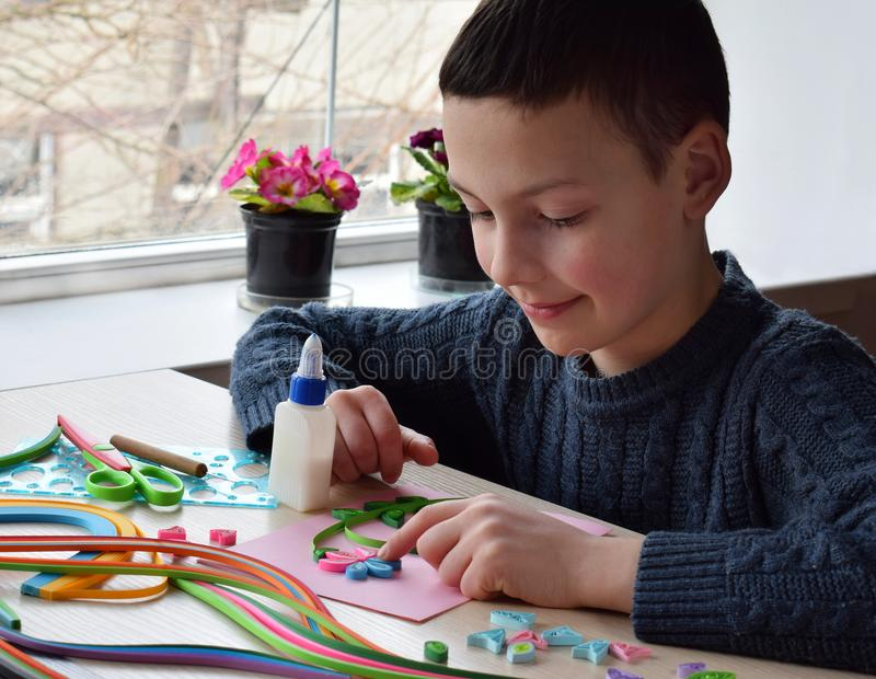 Quilling technique. Boy making decorations or greeting card. Paper strips, flower, scissors. Handmade crafts on holiday: Birthday, stock image