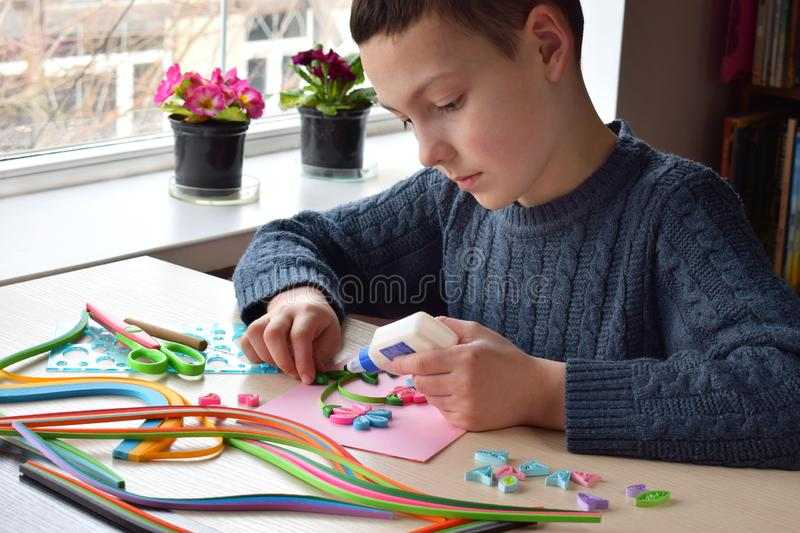 Quilling technique. Boy making decorations or greeting card. Paper strips, flower, scissors. Handmade crafts on holiday: Birthday royalty free stock image