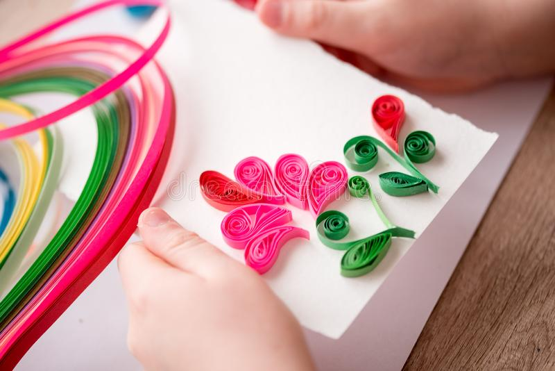 Quilling technique. Making decorations or greeting card. Paper strips, flower, scissors. Handmade crafts on holiday: Birthday, royalty free stock photo