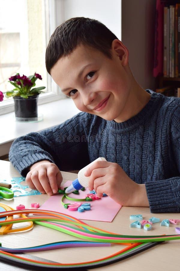 Quillingstechniek Jongen die decoratie of groetkaart maken Document stroken, bloem, schaar Met de hand gemaakte ambachten op vaka royalty-vrije stock afbeeldingen