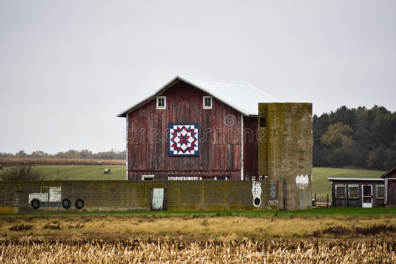 Quilt barn in Delavan, Wisconsin with cement wall and silo. A quilt barn in Delavan, Walworth County, Wisconsin. Cement wall with a truck painted on it. Cement stock images