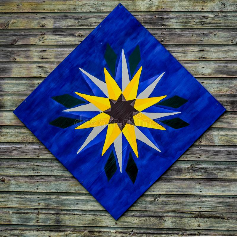 Quilt Block on Wooden Barn. A painted quilt block hanging on a wooden barn.  The quilt pattern is blue with a star shaped pattern of golden yellow royalty free stock photos