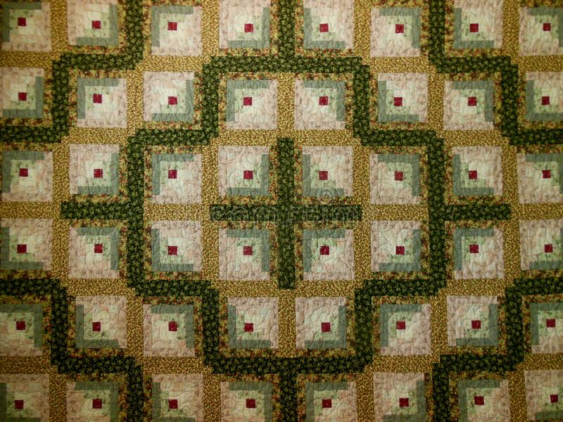 Quilt. Pattern with green, red, tans and whites made into blocks and squares royalty free illustration
