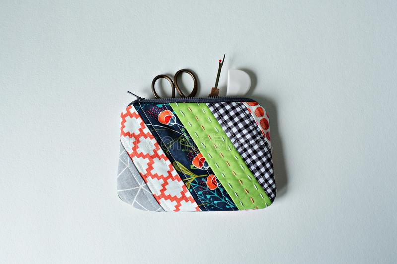 Quilted patchwork notion pouch, scissors and seam ripper. Over white royalty free stock photos