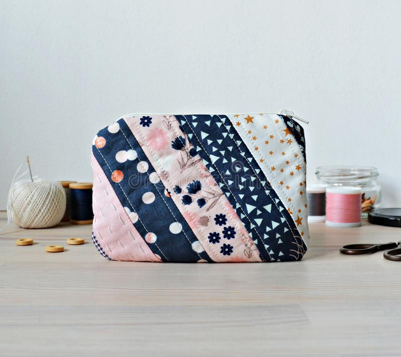 Quilted patchwork notion pouch, thread and buttons. On the wooden table stock images