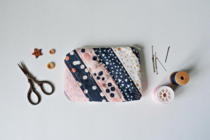 Quilted patchwork notion pouch, thread, metal pins, scissors and wooden buttons stock photo