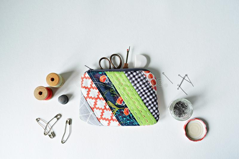 Quilted patchwork notion pouch, thread, metal pins, thimble, scissors and seam ripper. Over white stock images