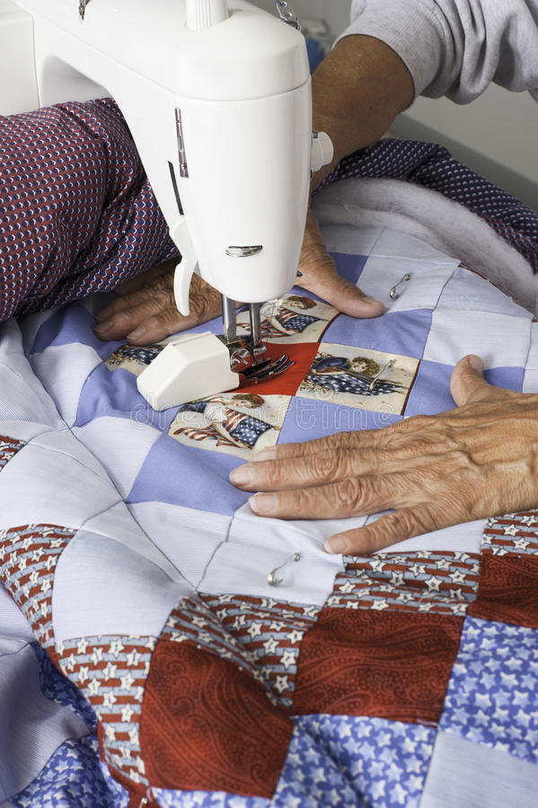 Quilter maskin som vadderar det patriotiska täcket arkivfoton