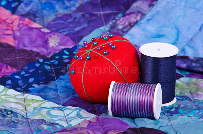 Quilting thread and pincushion. On the top of the quilt royalty free stock image