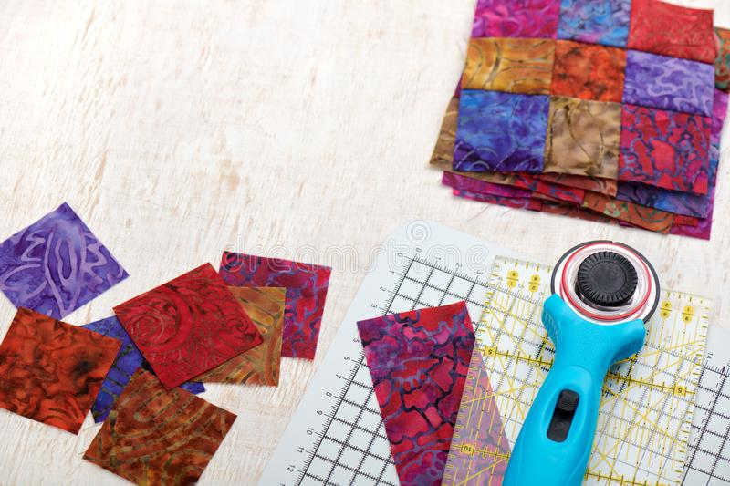 Quilting tools, sliced square bright pieces of batik, stack sewn blocks royalty free stock photography