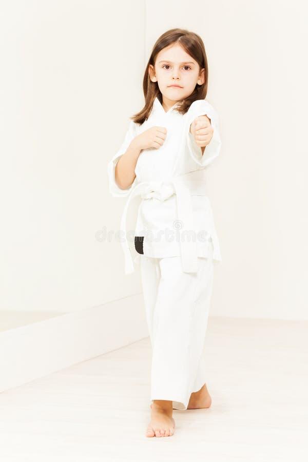 Quimono vestindo da menina do karaté que está na posição imagens de stock royalty free