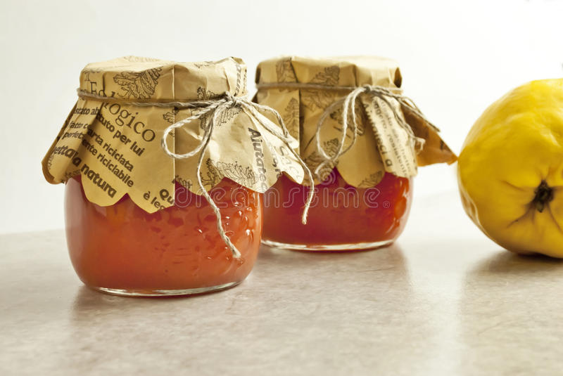 Quince marmalade. In jars and fruit stock photos